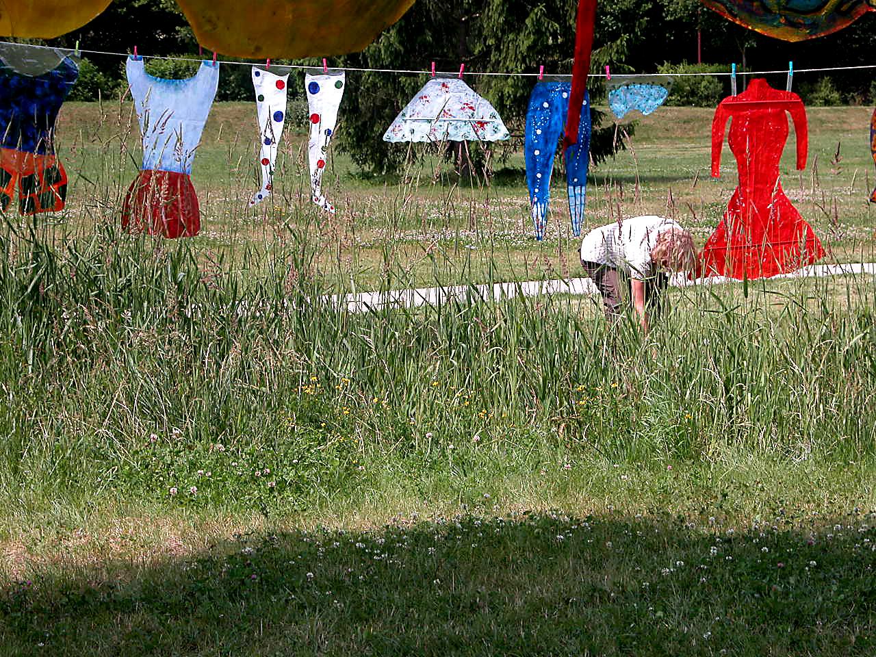 Habits en papier suspendus sur une corde passant entre les arbres