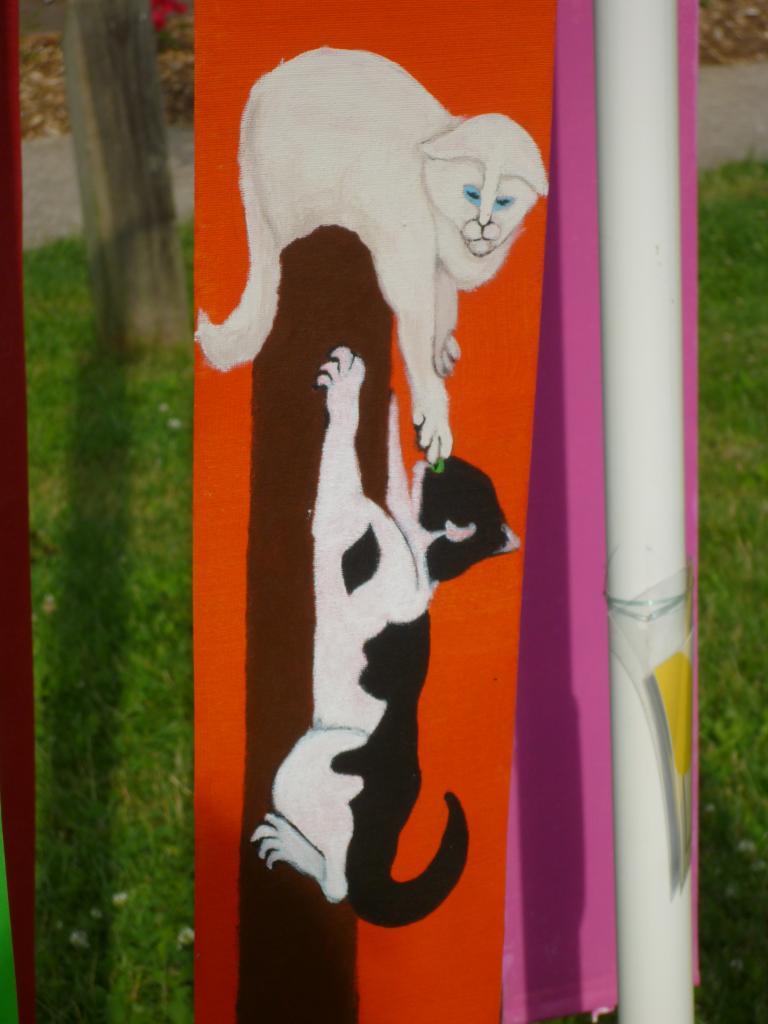 2 chats jouant ensemble sur un griffoir ( tissu pour store )